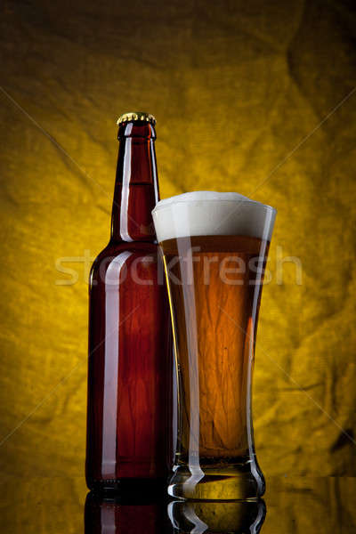 Beer in glass with bottle on yellow background Stock photo © artjazz