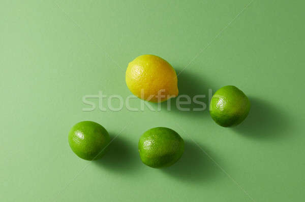 Citrus fruits on a green background. Top view of a group of green limes and one yellow lemon. Stock photo © artjazz