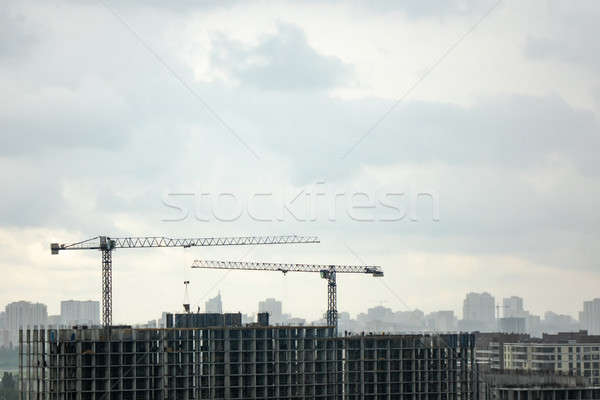 Building under construction with two tower cranes against a gray cloudy sky. Photo from the drone. Stock photo © artjazz
