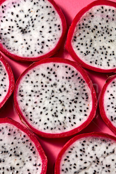 Flat lay view of background from round slices of Dragon fruit or Pitaya on a pink background. Stock photo © artjazz