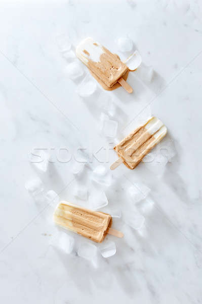 Creme brulee coffee ice cream on a wooden stick over marble background, top view. Stock photo © artjazz
