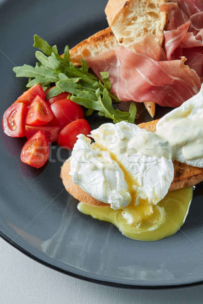 Eggs Benedict with bacon, toast and salad. Stock photo © artjazz