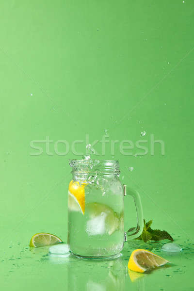 The cube of ice fell into a glass jar with a splash and drops of lemonade in different directions. D Stock photo © artjazz