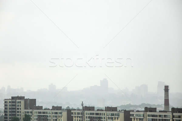 A view of the new houses against the background of the silhouettes of buildings in the misty sky. Stock photo © artjazz