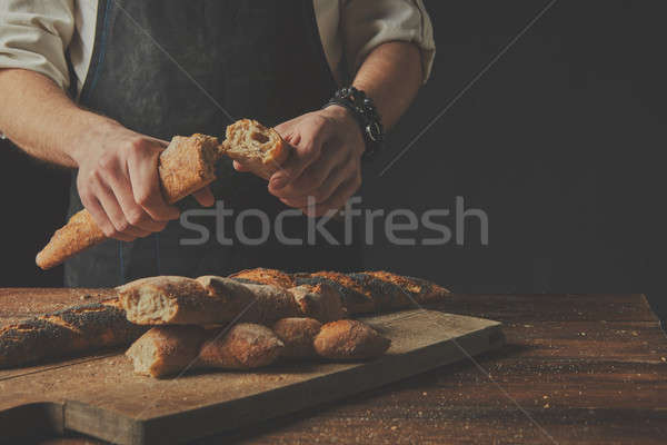 The baker keeps the baguette halves in his hands. Stock photo © artjazz