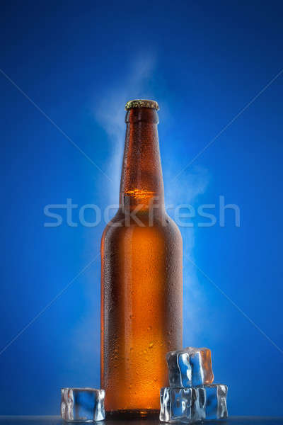 Stock photo: Cold beer bottle with drops, frost and vapour on blue