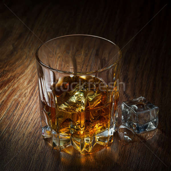 Whiskey with ice in glass on the wood Stock photo © artjazz