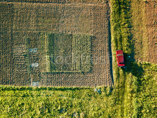 Aerial view of amid fields with red car on it Stock photo © artjazz