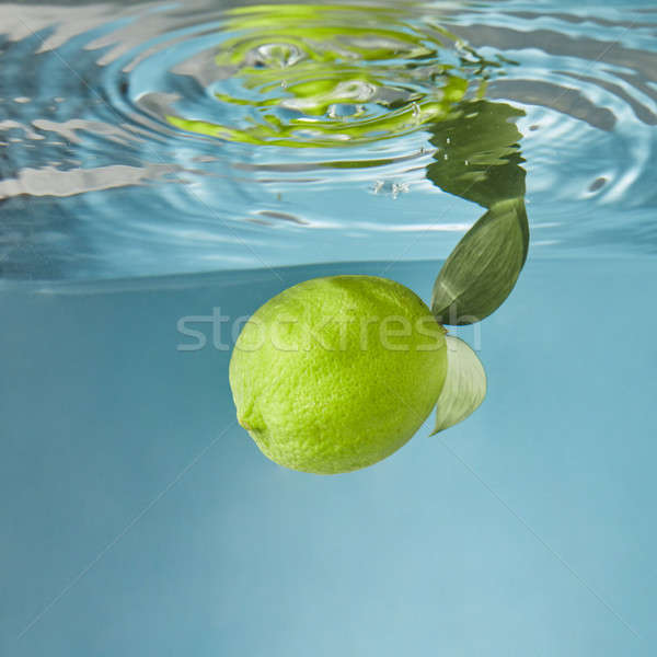 A whole green lime fresh, with green leaves falling down into th Stock photo © artjazz