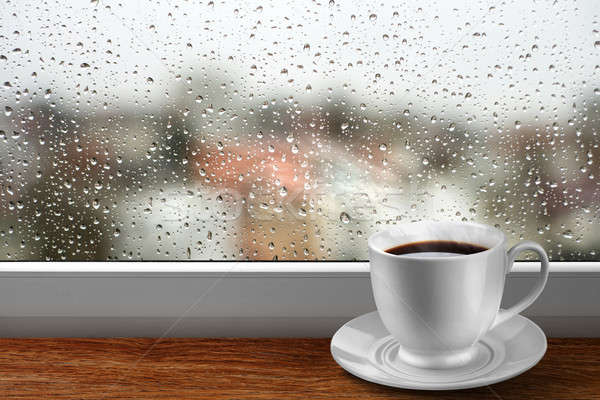 Coffee cup against window with rainy day view Stock photo © artjazz