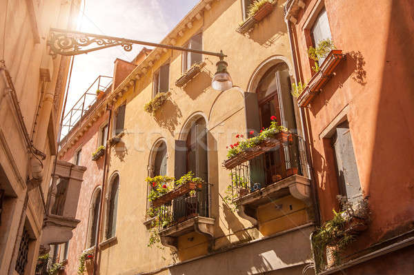 Beautiful old building balconies with colorful flowers Stock photo © artjazz