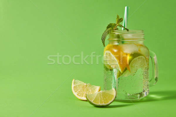 Refreshing cold non-alcoholic drink in glass jar with ice cubes, slices of lime and lemon, sprig of  Stock photo © artjazz