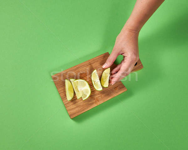A girl's hand takes a slice of ripe fresh green lime. Slices of natural lime on a wooden board on a  Stock photo © artjazz