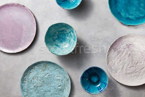 Set of porcelain handcraft plates or bowls on a gray table. Colorful ceramic vintage handmade dishes Stock photo © artjazz