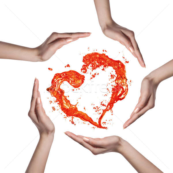 Stock photo: Red heart from water splash with human hands isolated on white