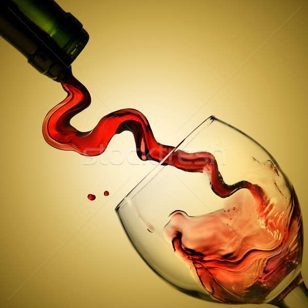 Pouring red wine in goblet on yellow background Stock photo © artjazz
