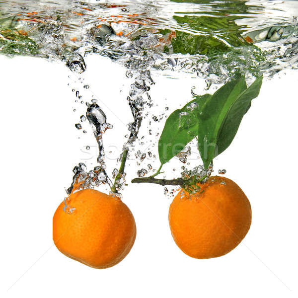 tangerines dropped into water with bubbles on white Stock photo © artjazz