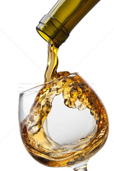 Cognac pouring into glass with splash isolated on white backgrou Stock photo © artjazz