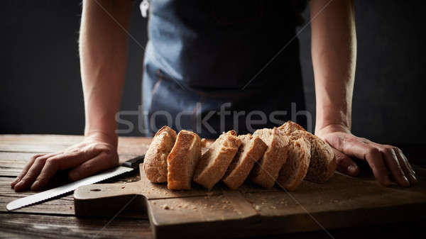 Whole grain bread put on a kitchen plate with a chef, Stock photo © artjazz