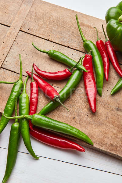 Stock photo: Chili colored peppers for cooking sauce on an old wooden board