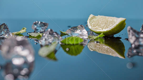 Lime fruit with ice isolated on blue background Stock photo © artjazz