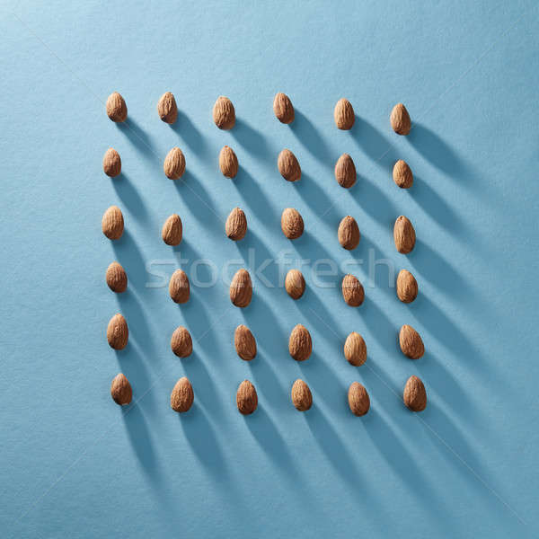 Almonds in a square shape in a blue paper background. Organic food Stock photo © artjazz