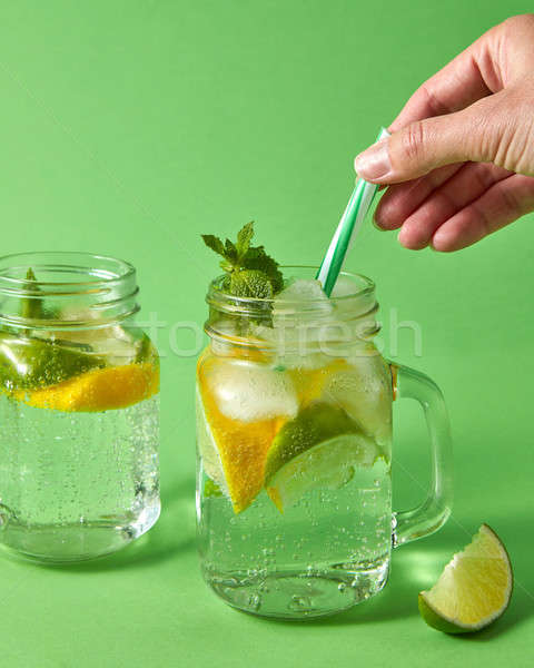 A woman's hand inserts plastic straws into a glass jar with lemonade from natural ingredients - wate Stock photo © artjazz