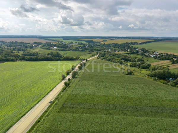 Bird's eye view from drone to a rural landscape with a village, dirt road and agricultural fields of Stock photo © artjazz