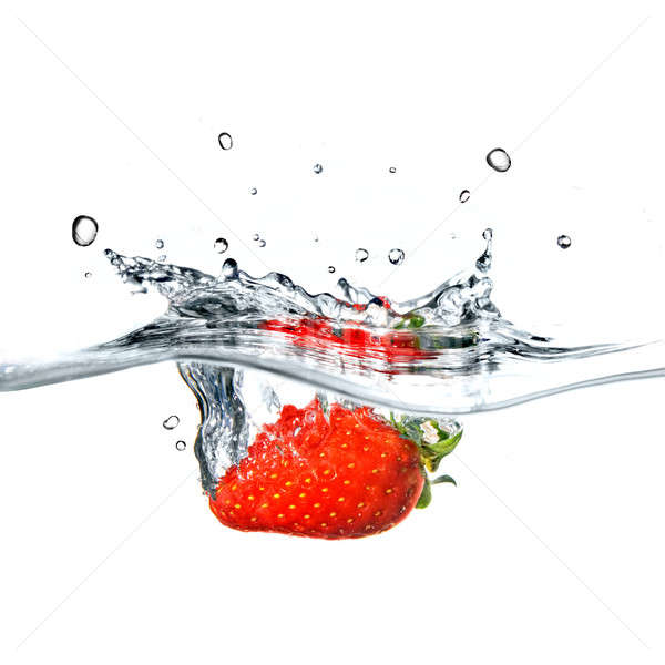 Fresh strawberry dropped into blue water with splash isolated on white Stock photo © artjazz
