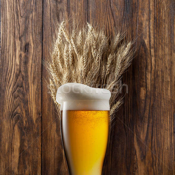 Glass of beer with wheat on wood Stock photo © artjazz