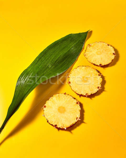 Beautiful composition of pieces of pineapple and green leaves on an orange paper background Stock photo © artjazz