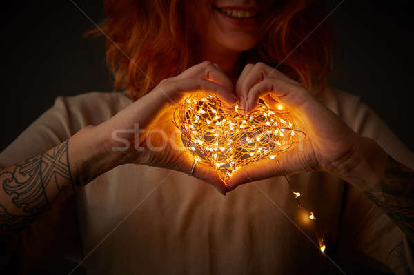 Happy red-haired girl holding garland in the shape of heart on a dark background. Festive card Stock photo © artjazz