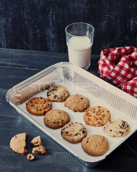 Baking tray with homemade cookies for Santa with peanuts, chocolate chips, raisins and a glass with  Stock photo © artjazz