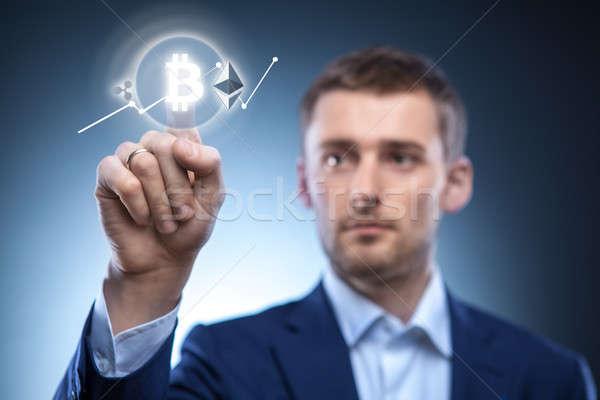 the man clicks Icon Bitcoin on virtual screen. Stock photo © artjazz