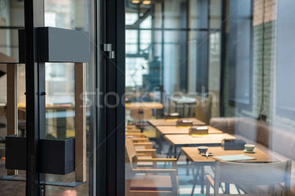 Modern door handle on the wooden glass door in front of the cafe. Stock photo © artjazz