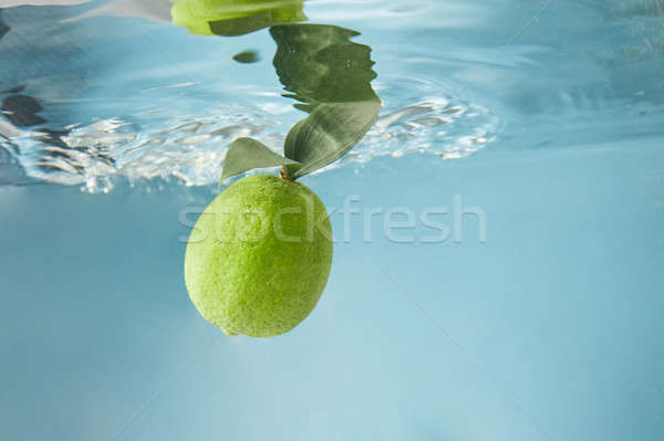 Fresh lime in water isolated on a blue background Stock photo © artjazz