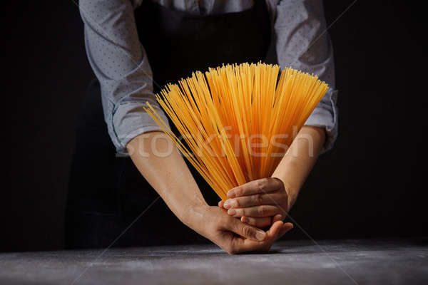 Fresh italian uncooked homemade pasta in female hands over a wooden table Stock photo © artjazz