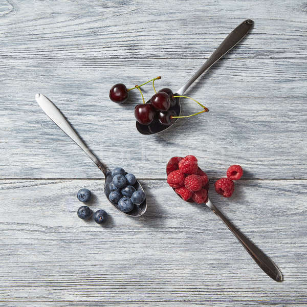 Three spoons with red juicy ripe berries - cherry, raspberry, blueberry and near them on a gray wood Stock photo © artjazz