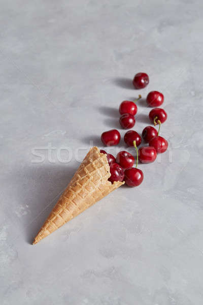 Sweet wafer cone with freshly picked red cherries on a gray background. Stock photo © artjazz