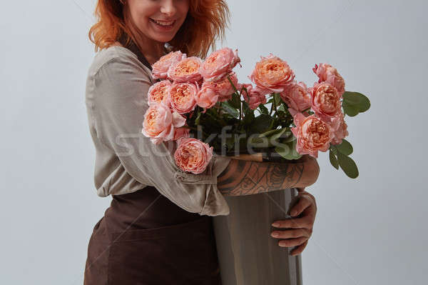 Smiling girl in a brown apron with a tattoo holds a beautiful bouquet of pink roses in a vase on a g Stock photo © artjazz