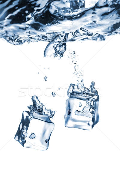 Stock photo: ice cubes dropped into water with bubbles isolated on white
