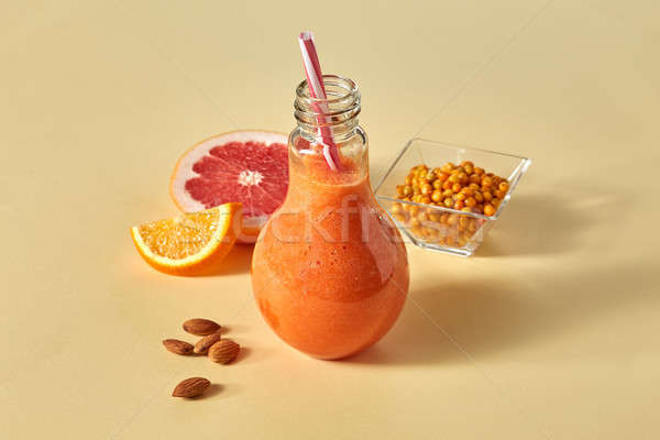 Orange smoothies with citrus, carrots, sea buckthorn and almonds on an orange paper background Stock photo © artjazz