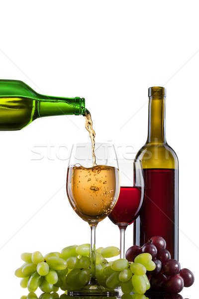White wine pouring into glass with grape and bottles isolated Stock photo © artjazz