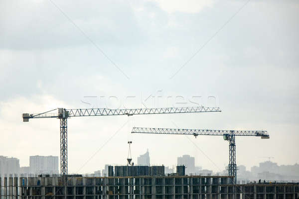 Industrial landscape with silhouettes of cranes on the gray cloudy background. Stock photo © artjazz
