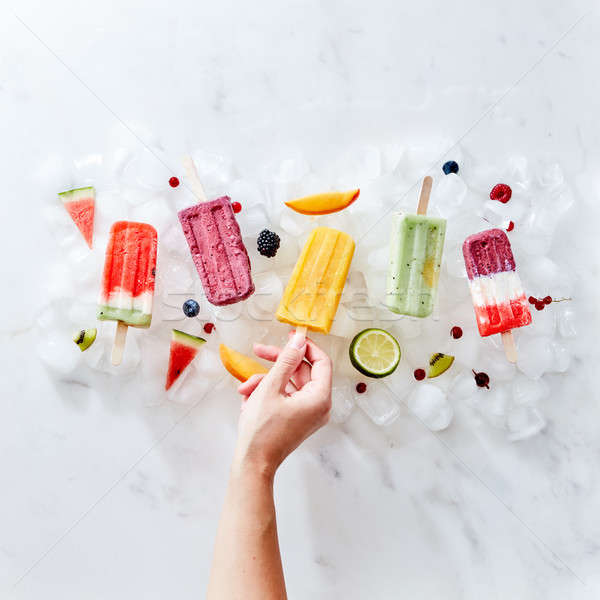 A woman's hand holds a frozen fruit smoothie on a stick against the background of ice cubes with ber Stock photo © artjazz