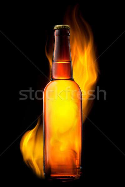 Beer bottle in fire on black Stock photo © artjazz