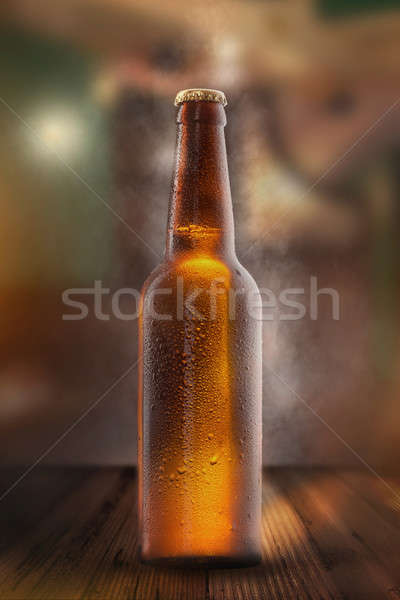 Cold beer bottle with drops, frost and vapour Stock photo © artjazz