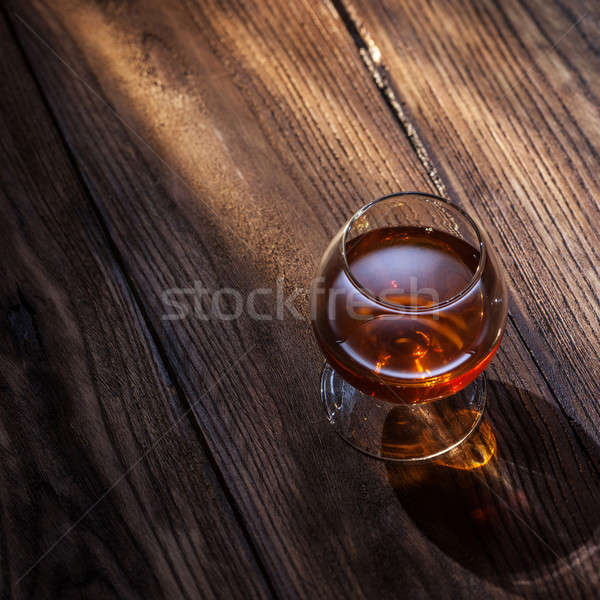 Cognac in glass on the wood Stock photo © artjazz