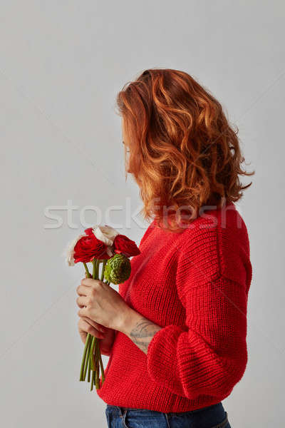 Young woman with lush red hair with a bunch of fresh Ranunculus on gray background with copy space. Stock photo © artjazz