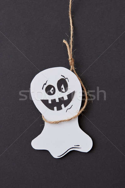 Halloween greeting card with laughing flying scary Casper hanging from a rope handmade from paper on Stock photo © artjazz